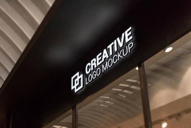 店の入り口に光の効果を持つ3dロゴのモックアップ