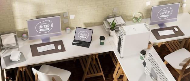 オフィスデスクコンピュータデバイスのモックアップを使用した3dレンダリングオフィスルームのインテリアデザイン
