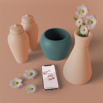 3d vases with flowers beside phone