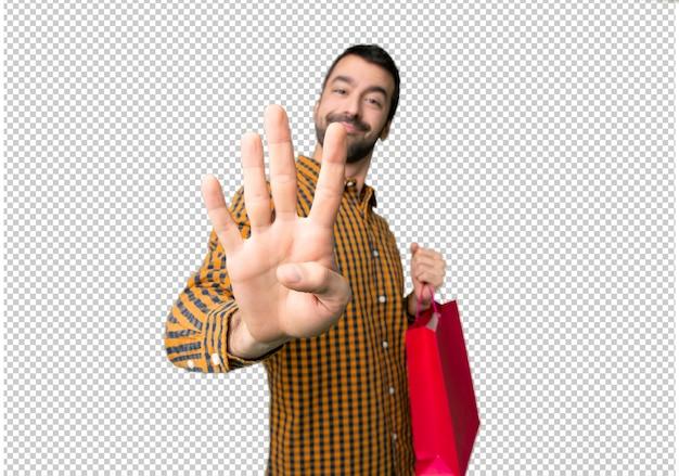 幸せな買い物袋を持つ男と指で4つを数える