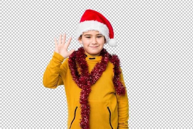 サンタの帽子をかぶっているクリスマスの日を祝う少年は、指で5を示す陽気な笑顔を分離しました。