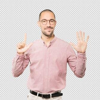 彼の手で数7のジェスチャーをして幸せな若い男