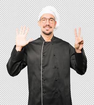 彼の手で数7のジェスチャーを行う幸せな若いシェフ