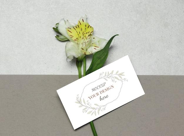 灰色のベージュ色の背景上の花とモックアップ名刺