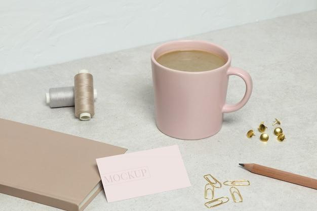 Макет визитки, розовая книга, золотой карандаш, скрепки, булавки и нитки, чашка кофе на гранитной фактуре