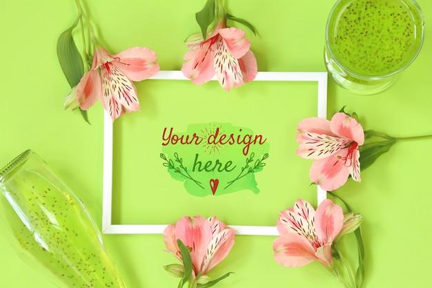 Макет фоторамка с красивыми цветами на зеленом фоне