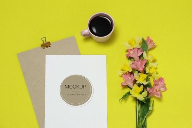 花、一杯のコーヒーと黄色の背景にモックアップ紙フレーム