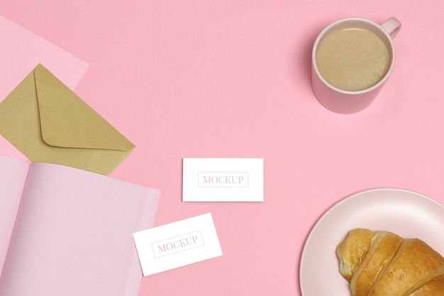 Визитные карточки макета на розовом столе с чашкой и тортом