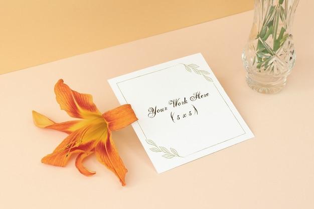 花とベージュ色の背景にモックアップのウェディングカード