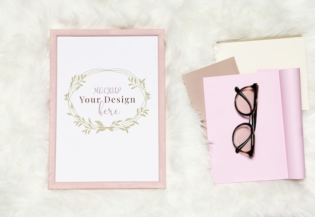 ノートブックとメガネのスタックを持つ白い毛皮のような背景のモックアップフォトフレーム