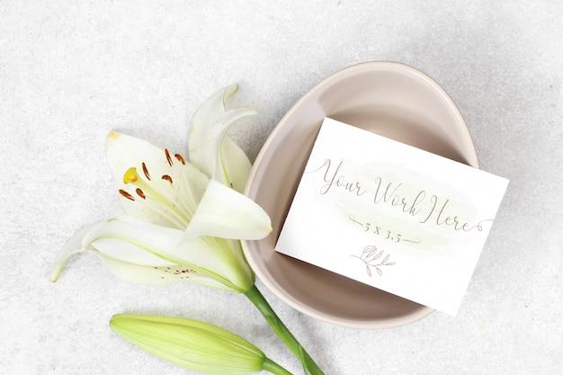 灰色の背景の上に花とモックアップのウェディングカード