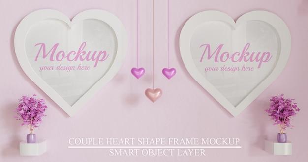 ピンクの壁にカップルホワイトハート形フレームモックアップ