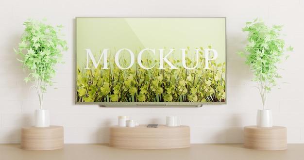 木製の装飾テーブルが付いている白い壁に取り付けられた画面テレビのモックアップ