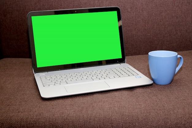 茶色の背景に茶色のカップを持つブランクスクリーンラップトップ