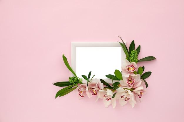 Фоторамка украшена зелеными листьями и цветами орхидеи