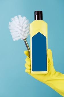 Рука в желтой перчатке держит бутылку жидкого моющего средства для туалета и щетки.