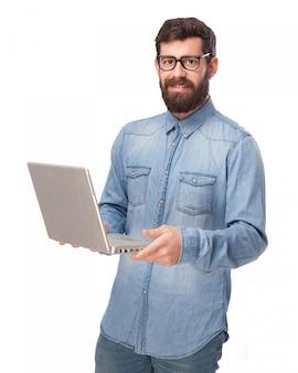 Молодой человек держит свой ноутбук