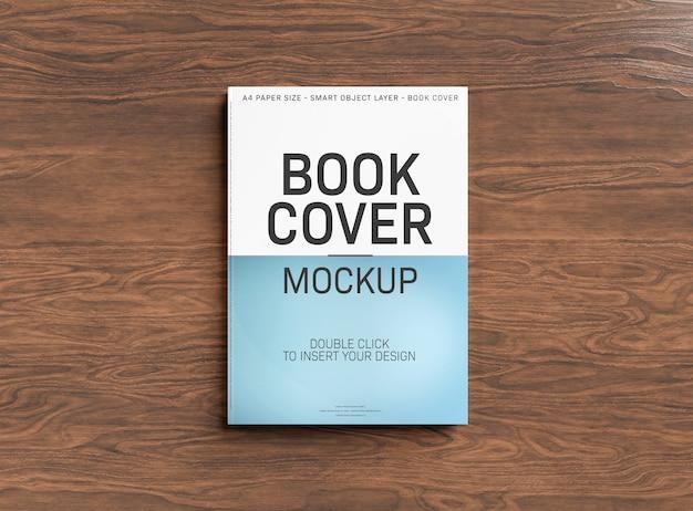 木製の表面の本の表紙のモックアップ