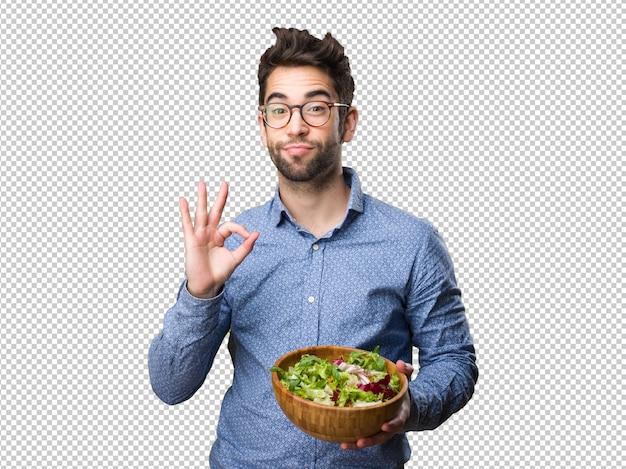 大丈夫ジェスチャーをしているサラダを保持している若い男