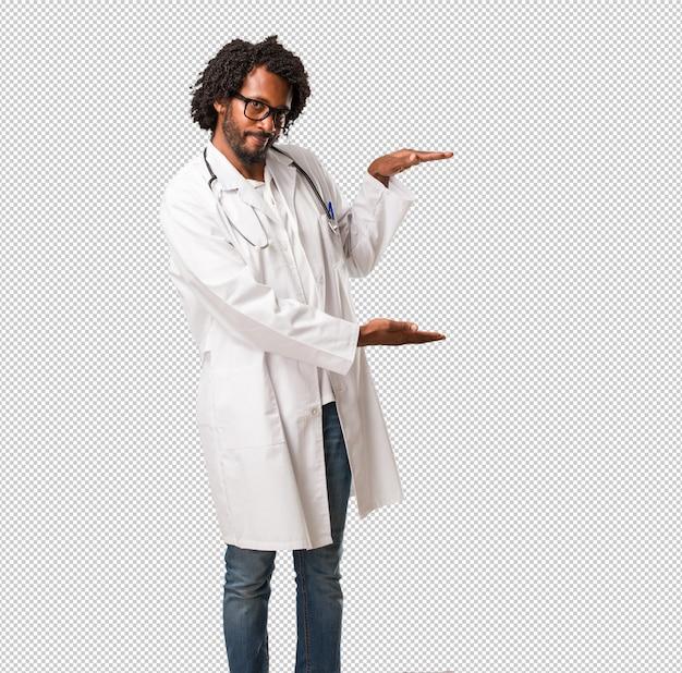Красивый афро-американский врач держит что-то с руками