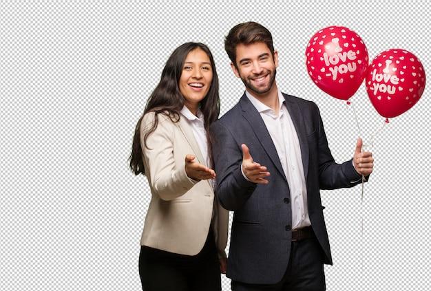 Молодая пара в день святого валентина, протягивая руку, чтобы приветствовать кого-то