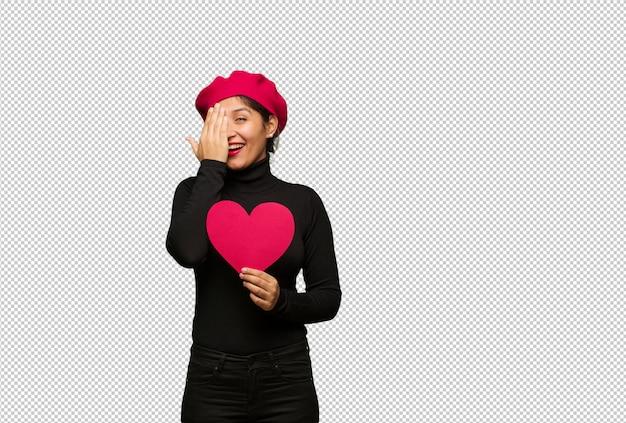 幸せな叫びと手で顔を覆っているバレンタインデーの若い女性