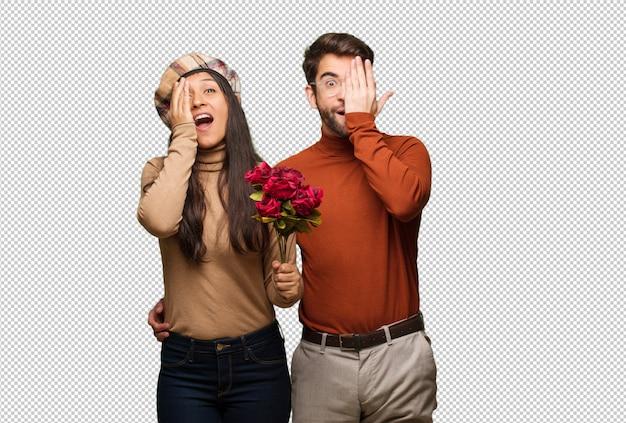 幸せな叫びと手で顔を覆っているバレンタインデーの若いカップル