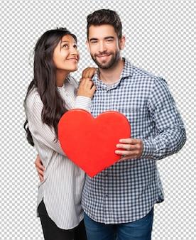 Молодая пара держит красное сердце