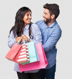 買い物袋を保持している若いカップル