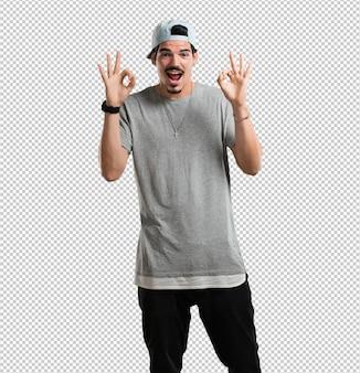 Молодой рэпер человек веселый и уверенный делает хорошо жест, взволнован и кричит