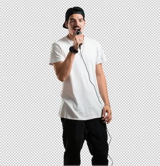 Молодой рэпер человек счастлив и мотивирован, поет песню с микрофоном