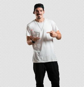 Молодой рэппер человек улыбается и счастлив, держа в руках миниатюрную корзину, концепция покупок