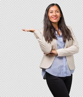 若いビジネスインド人女性の手で何かを保持している製品を表示