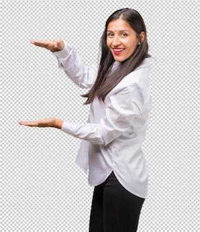 製品を示す、手で何かを保持している若いインド人女性の肖像画