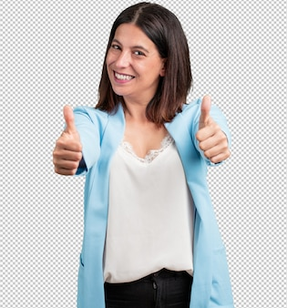 Среднего возраста женщина веселая и возбужденная, улыбается и поднимает большой палец вверх