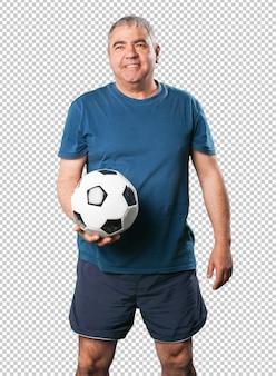 中年の男性がサッカーボールを保持