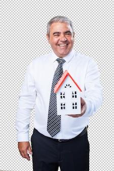 Счастливый зрелый человек держит дом
