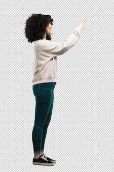 Полное тело молодая женщина, указывая в сторону