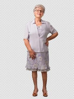 Полное тело старшей женщины с руками на бедрах, стоя, расслабленной и улыбчивой, очень позитивной и веселой