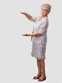 Полное тело старшая женщина держит что-то с руками, показывая продукт, улыбаясь и веселый, предлагая воображаемый объект