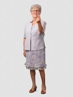 Полное тело старшая женщина приглашает прийти, уверенный и улыбающийся, делая жест рукой, будучи позитивным и дружелюбным