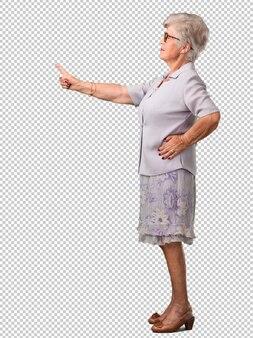 フルボディの年配の女性が側面を指して、笑みを浮かべて驚いた、自然でカジュアルな何かを提示