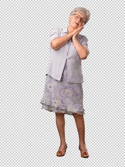 Полное тело старшей женщины уставшее и очень сонное, выглядит комфортно и расслабленно, сон жест