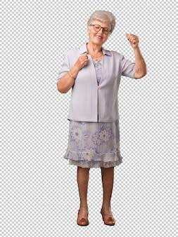 Полное тело старшая женщина слушать музыку, танцевать и веселиться, двигаться, кричать и выражать счастье, концепция свободы