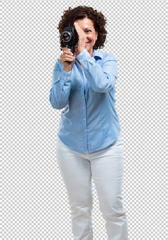 Среднего возраста женщина взволнована и развлекается, смотрит в пленочную камеру