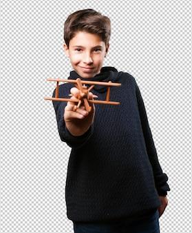 白の木製の飛行機を持った少年