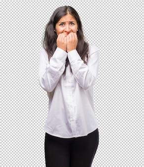爪をかむ、緊張し、非常に心配し、将来を怖がっている若いインド人女性の肖像画は、パニックとストレスを感じています