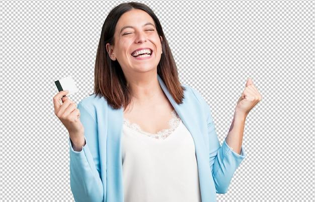 Среднего возраста женщина веселая и улыбающаяся, очень взволнованная, держит новую банковскую карту, готова пойти за покупками