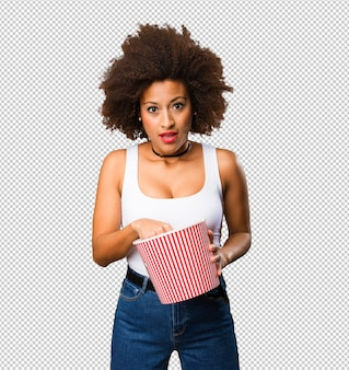Молодая черная женщина, держащая ведро попкорна