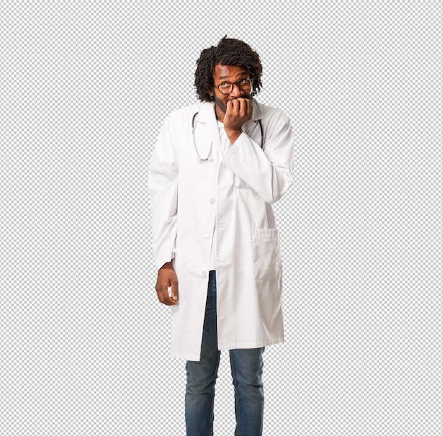 ハンサムなアフリカ系アメリカ人の医師が爪をかむ、神経質で非常に不安で将来のために怖がって、パニックとストレスを感じる